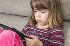 Liten flicka som spelar med en digital minnestavla Fotografering för Bildbyråer