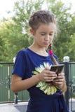 Liten flicka som spelar med en smartphone utomhus Fotografering för Bildbyråer