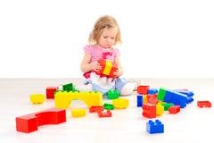 Liten flicka som spelar med färgrika kvarter arkivfoton