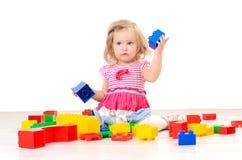 Liten flicka som spelar med färgrika kvarter royaltyfria bilder