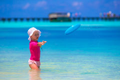 Liten flicka som spelar med flygdisketten på vit Arkivbilder