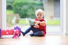 Liten flicka som spelar med hennes docka Fotografering för Bildbyråer