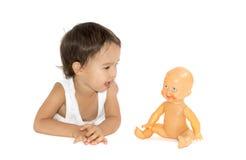 Liten flicka som spelar med hennes docka i studio isolerat Royaltyfria Bilder