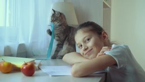 Liten flicka som spelar med hennes husdjurkatt och ser kameran arkivfilmer