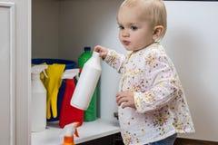 Liten flicka som spelar med hushållrengöringsmedel Fotografering för Bildbyråer