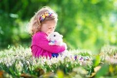 Liten flicka som spelar med kaninen på jakt för påskägg Arkivbild