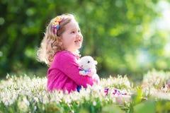 Liten flicka som spelar med kaninen på jakt för påskägg Fotografering för Bildbyråer