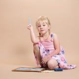 Liten flicka som spelar med krita Arkivbilder