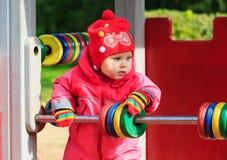 Liten flicka som spelar med kulrammet på lekplats Arkivbilder