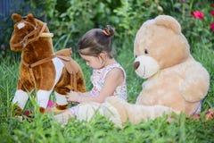 Liten flicka som spelar med leksaker på grönt gräs utanför i trädgård royaltyfri bild