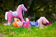 Liten flicka som spelar med leksakhästen i cowboydräkt Arkivbild