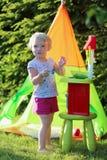 Liten flicka som spelar med leksakkök utomhus Arkivbild