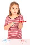 Liten flicka som spelar med målarfärg Arkivbild
