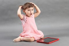 Liten flicka som spelar med minnestavladatoren på golvet royaltyfri bild