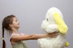 Liten flicka som spelar med mjuka leksaker Arkivbild