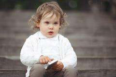 Liten flicka som spelar med mobiltelefonen Arkivfoton