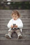Liten flicka som spelar med mobiltelefonen Arkivbilder