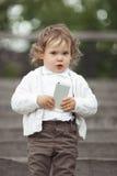 Liten flicka som spelar med mobiltelefonen Arkivbild