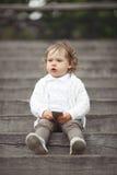 Liten flicka som spelar med mobiltelefonen Arkivfoto