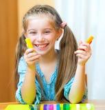 Liten flicka som spelar med plasticine Arkivbild