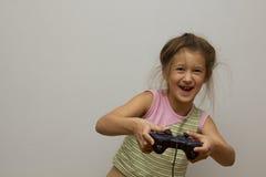 Liten flicka som spelar med playstationstyrspaken Fotografering för Bildbyråer
