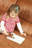 Liten flicka som spelar med pusselstycken Arkivbild