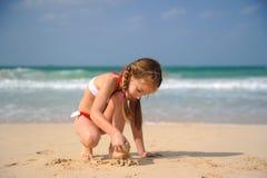 Liten flicka som spelar med sand arkivbilder