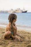 Liten flicka som spelar med sand på en strand och blickar på skepp arkivbild
