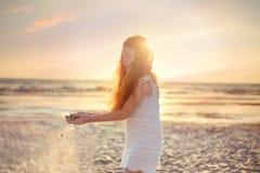 Liten flicka som spelar med sand, solnedgånghimmel på Adriatiskt havstranden i Albanien Sand som halkar till och med fingrar för  Royaltyfria Foton