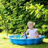 Liten flicka som spelar med sandlådan i trädgården Fotografering för Bildbyråer