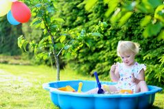 Liten flicka som spelar med sandlådan i trädgården Royaltyfri Bild