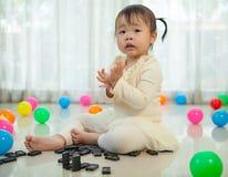 Liten flicka som spelar med svart dominobricka Arkivbild