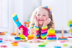 Liten flicka som spelar med träleksaker Arkivfoto