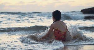 Liten flicka som spelar med vågorna på stranden under solnedgång stock video