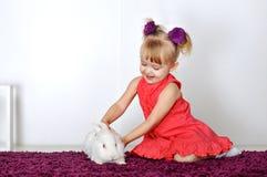 Liten flicka som spelar med vit kanin Arkivbild