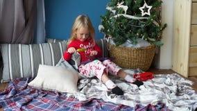Liten flicka som spelar minnestavlaPC i jul arkivfilmer