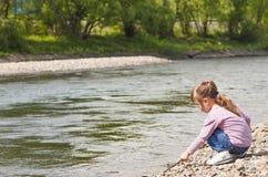 Liten flicka som spelar nära floden Royaltyfri Fotografi