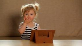 Liten flicka som spelar på en minnestavla lager videofilmer