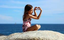 Liten flicka som spelar på havframdelen i havet för Los Cabos Mexico semesterortklippa Royaltyfri Fotografi