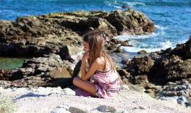 Liten flicka som spelar på havframdelen i havet för Los Cabos Mexico semesterortklippa Royaltyfri Bild