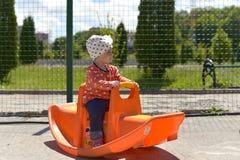 Liten flicka som spelar på lekplatsen på en varm solig dag royaltyfria foton