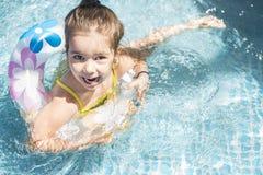 Liten flicka som spelar på swimmingpoolen Fotografering för Bildbyråer
