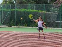Liten flicka som spelar tennis på domstolen arkivbild
