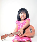 Liten flicka som spelar ukulelet Arkivbild