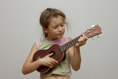 Liten flicka som spelar ukulelet Fotografering för Bildbyråer