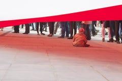 Liten flicka som spelar under en enorm flagga Fotografering för Bildbyråer