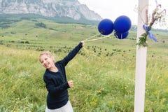 Liten flicka som spelar utomhus med ballonger royaltyfri foto
