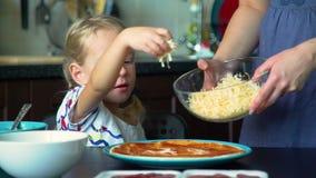 Liten flicka som strilar ost på pizzagrund arkivfilmer
