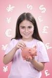 Liten flicka som sätter in ett mynt in i en spargris Arkivbilder