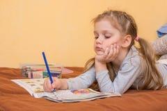 Liten flicka som studerar en tidskrift med blyertspennan i hans hand som ligger på hans mage och hans huvud i hans begagnat Arkivbild